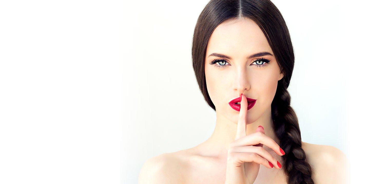 belle femme brune avec une longue tresse sur le coté et des lèvres rouges, signalant un secret avec ses doigts