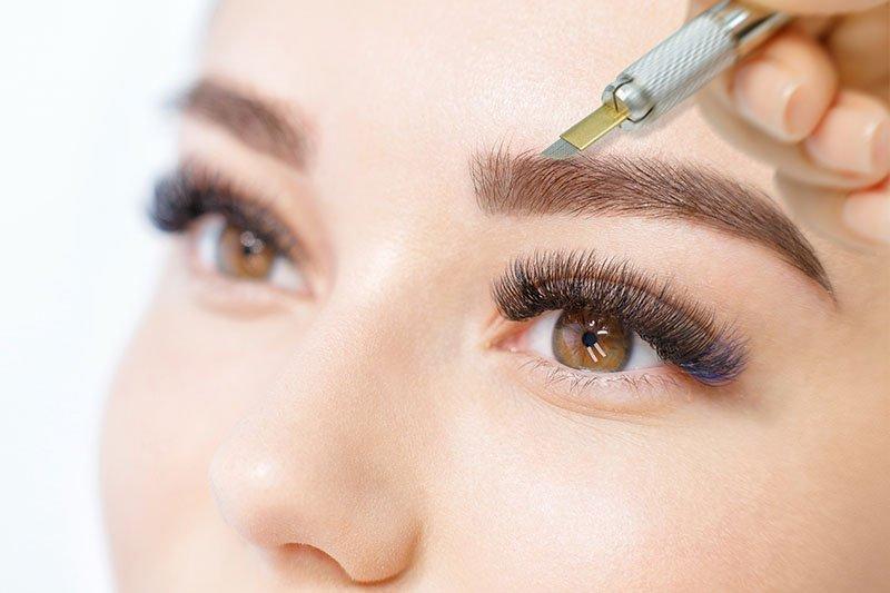 jeune femme avec de longs cils recevant un soin de microblading des sourcils