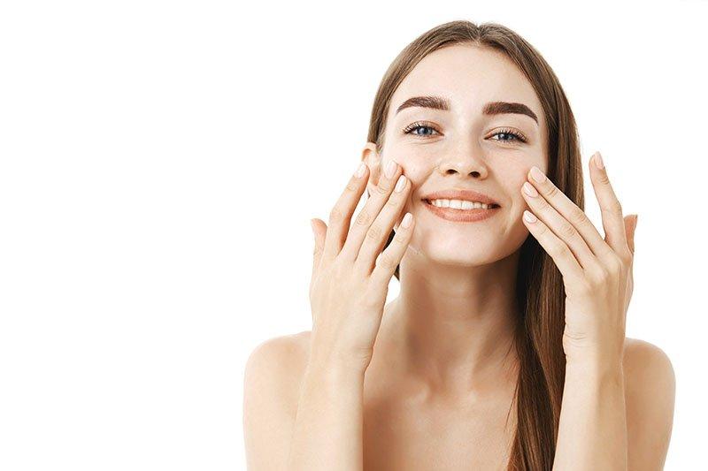 jeune femme souriant et caressant son visage