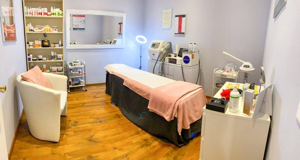 vue grand angle de la cabine de soins de l'institut avec table de massage, machines de soins esthétiques et fauteuil confortable