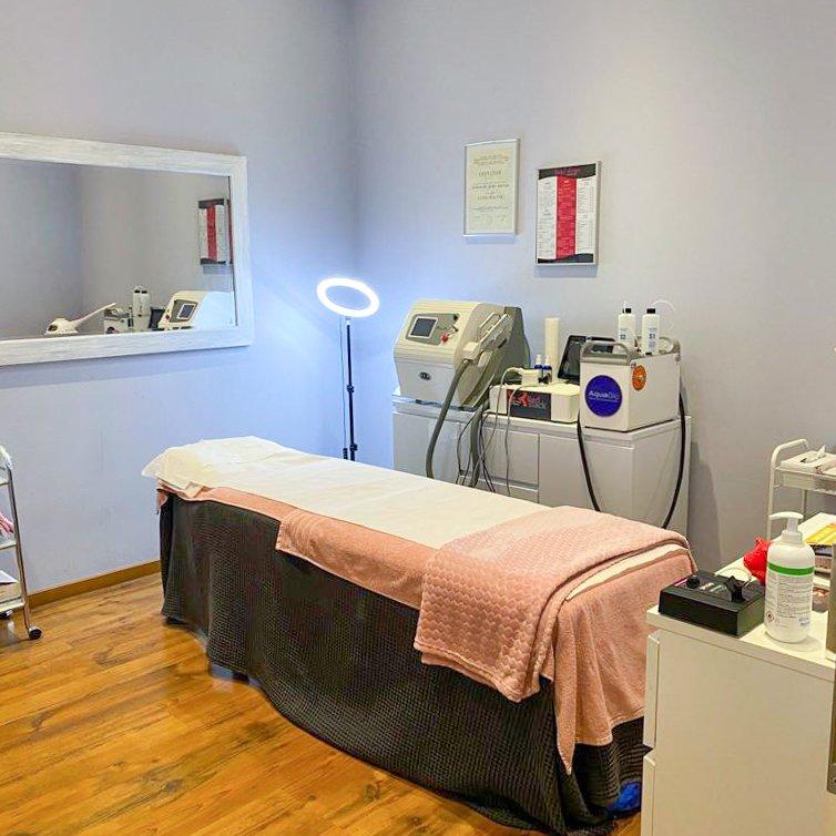 cabine de l'institut avec table de massage pour soins esthétique, mirroir et machines de soins esthétiques